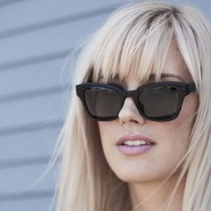 Woman wearing black tinted frieze frames glasses