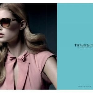 A woman wearing Tiffany and co glasses and a pink dress