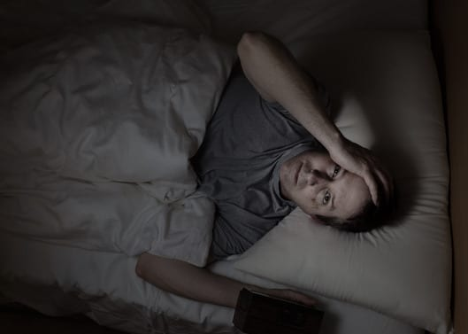 Top view image of mature man, looking forward, having trouble sleeping from blue light exposure